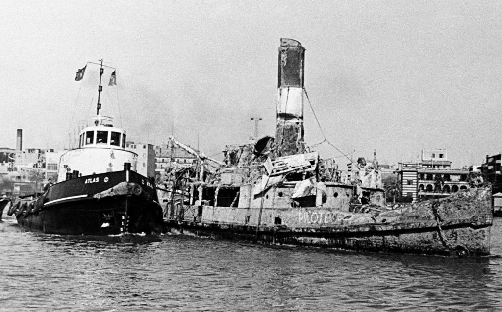 A wreck is towed away as part of the clearance operations in the Suez Canal (1 January 1957)